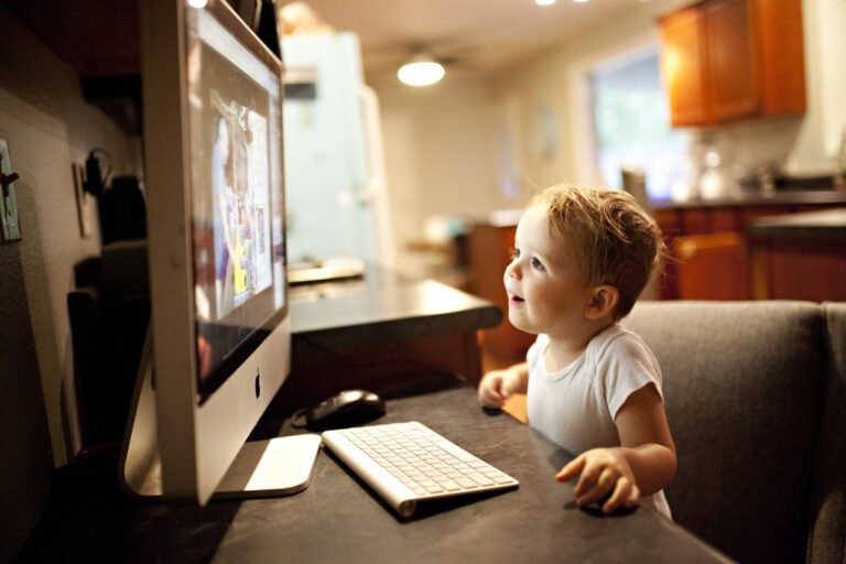 toddler looking at a computer screen while sitting in the kitchen in a white onsie talking to t20 LABGgZ