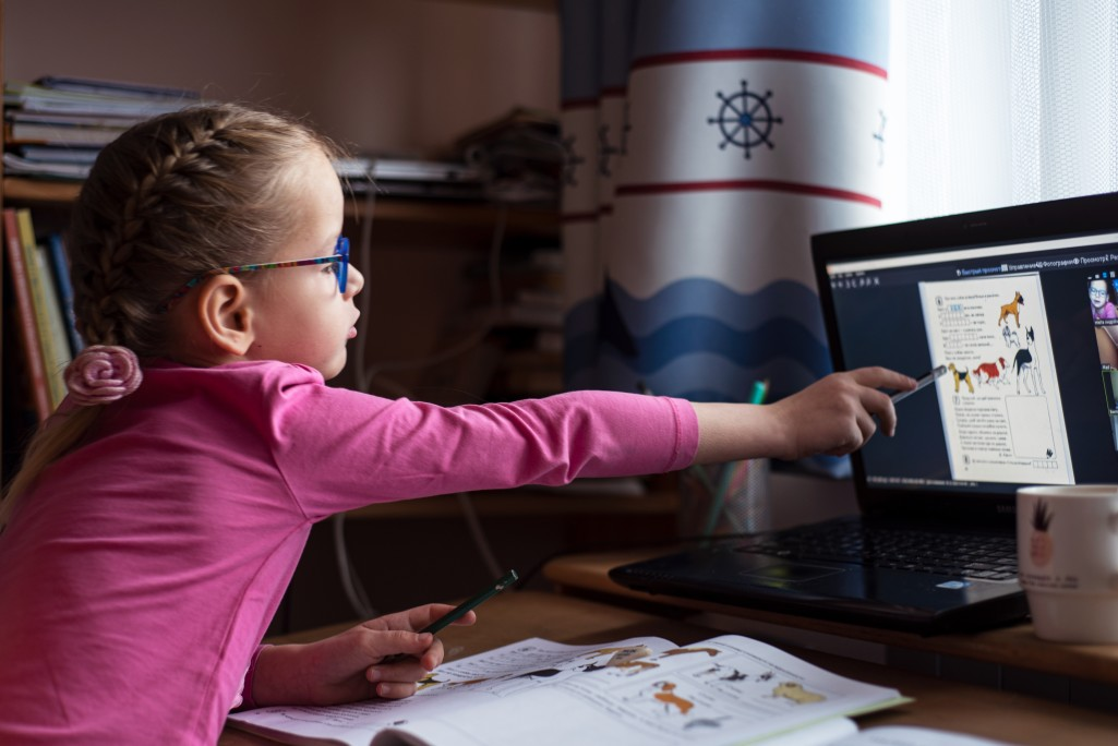 little girl in eyelgasses studying online and using her laptop at home t20 aaJL1x